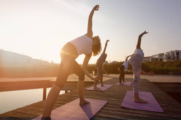group of women exercising yoga on jetty in the city at sunrise A group of four women is practicing yoga on a jetty at, a yoga instructor is teaching them. The women are mixed age range, it is the time short after sunrise, the lake is Phoenixsee in Dortmund, Germany, they are doing the warrior pose, the photo is backlit yoga class stock pictures, royalty-free photos & images