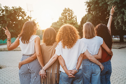 Group of women friends holding hands together against sunset