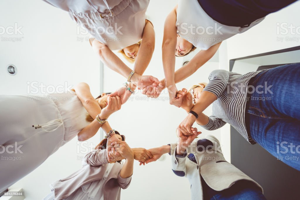 Group of women holding hands in circle Women's team. Group of woman at training, standing in circle and holding hands. Low angle view. Adult Stock Photo