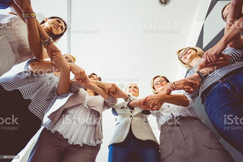 Group of women holding hands Women's team. Group of woman at training, standing in circle and holding hands. Low angle view. Adult Stock Photo