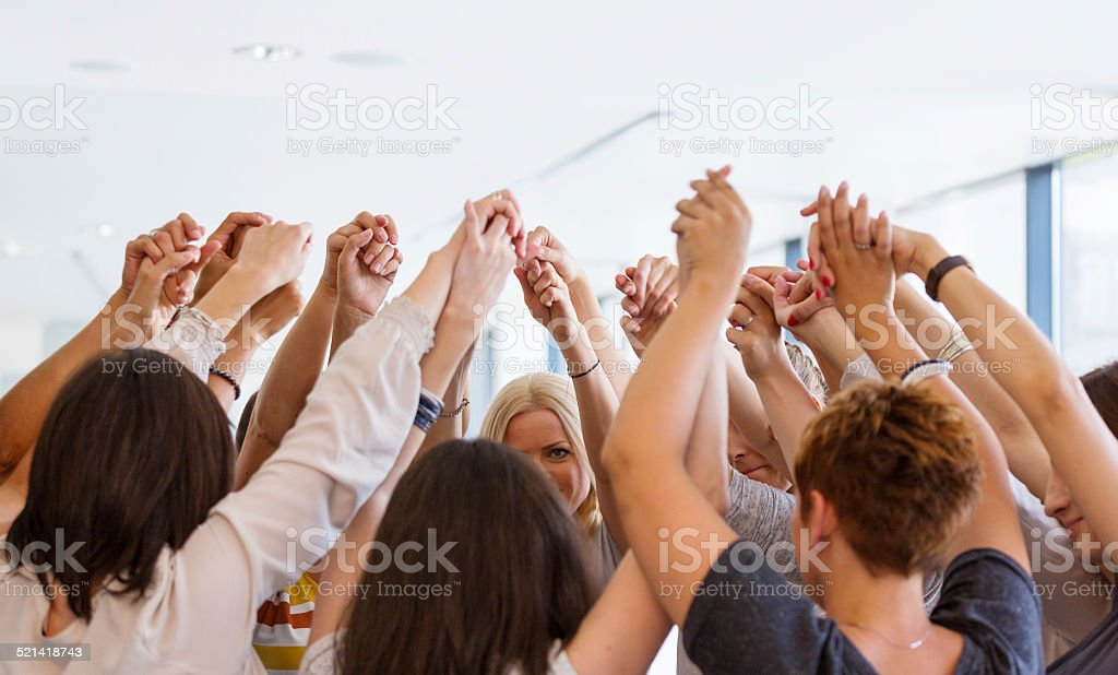 Group of women holding hands. Unity concept Group of women standing toghether in the circle and holding raised hands. Unity concept.  Achievement Stock Photo