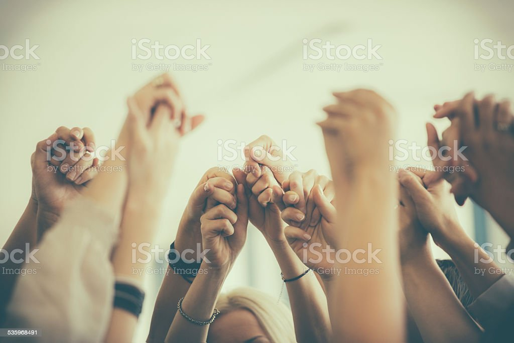 Group of women holding hands. Unity concept Group of women standing toghether in the circle and holding raised hands. Close up of hands. Unrecognizable people.  2015 Stock Photo