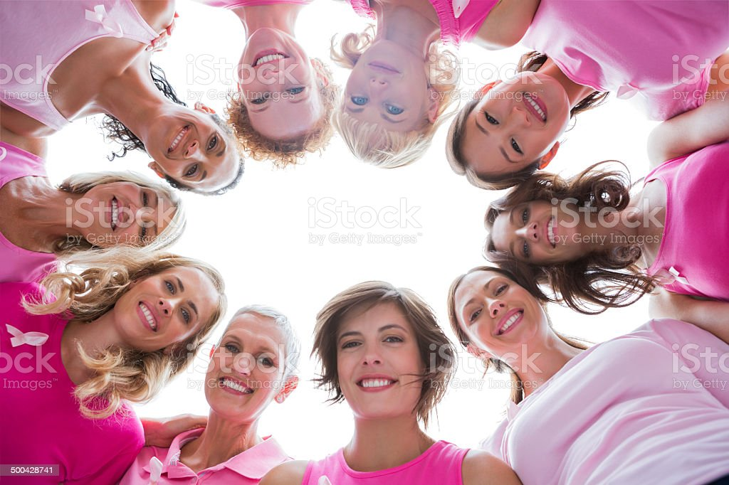 Group of women in circle wearing pink for breast cancer stock photo