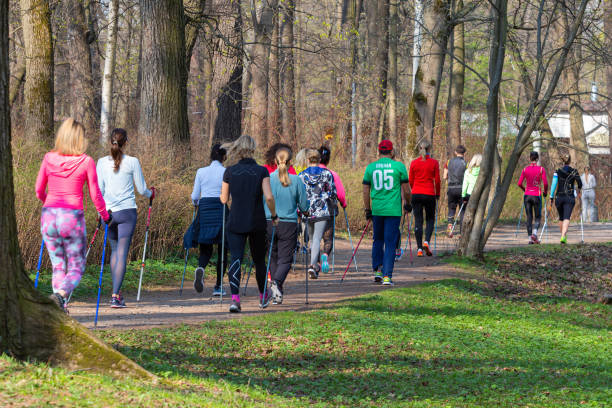 group of women in sportswear are walking in the park stock photo