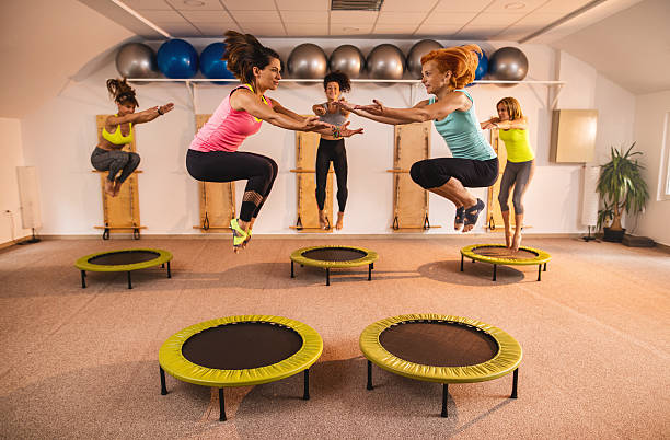 group of women jumping on trampolines during pilates exercise class. - trampolín artículos deportivos fotografías e imágenes de stock