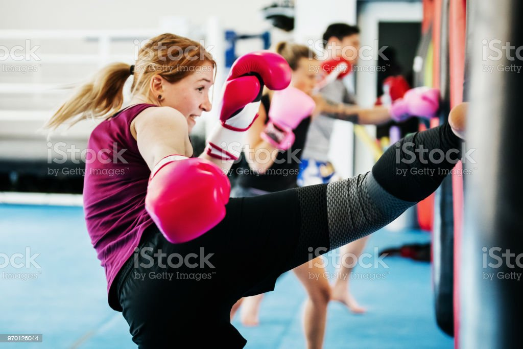 Group Of Women Kickboxing Together At Gym stock photo