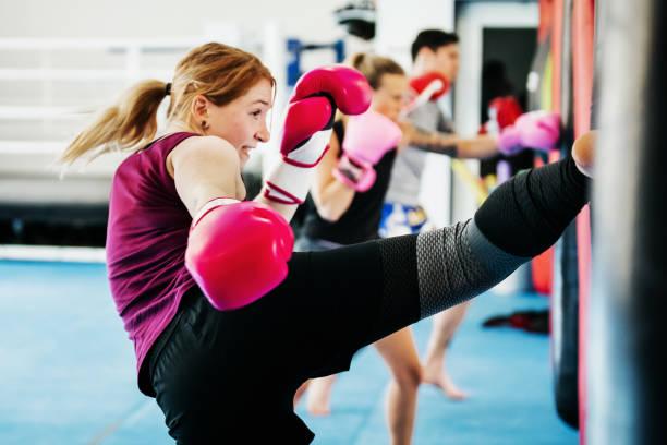 gruppe von frauen kickboxen gemeinsam in der turnhalle - asiatischer kampfsport stock-fotos und bilder