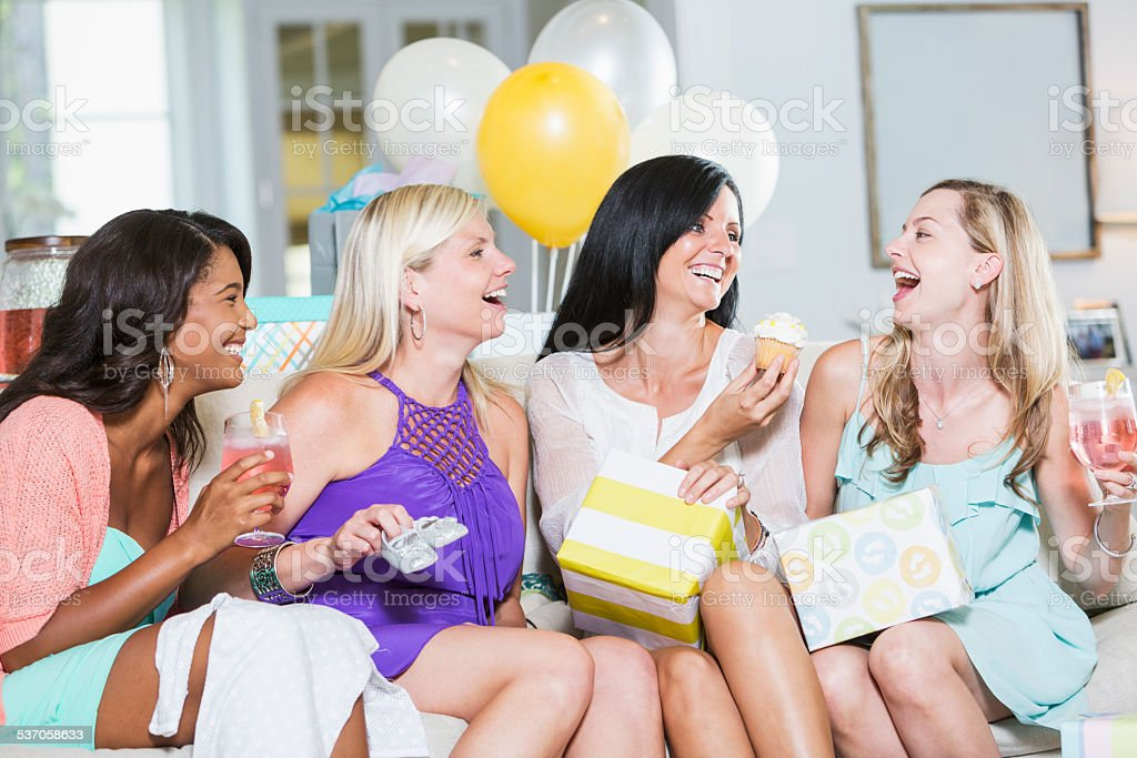 Group of women laughing at baby shower stock photo