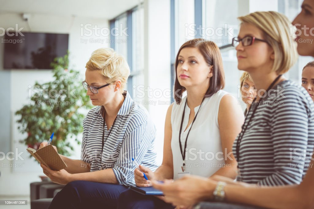 Group of women listening to a presentation Group of women listening to a presentation. Group of female business professional sitting at a seminar and paying attention to the presenter. Achievement Stock Photo