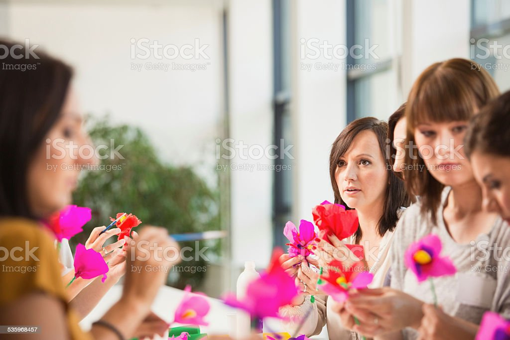 Group of women making paper flowers Group of women working on workshop, making coloful paper flowers. 2015 Stock Photo