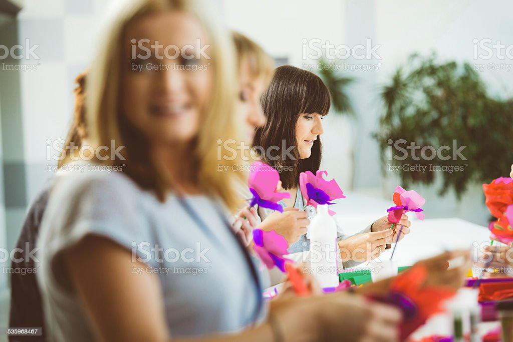 Group of women making paper flowers Group of women attending a workshop, making coloful paper flowers. 2015 Stock Photo