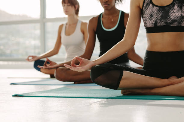 Group of women meditating in Padmasana yoga Female sitting on fitness mat with legs crossed and hands on knees in yoga pose. Group of women meditating in lotus pose at yoga class, Padmasana. yoga class stock pictures, royalty-free photos & images