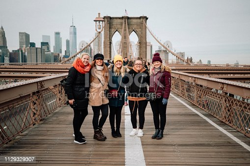 Five women standing side-by-side for a photo on Brooklyn Bridge, New York City.