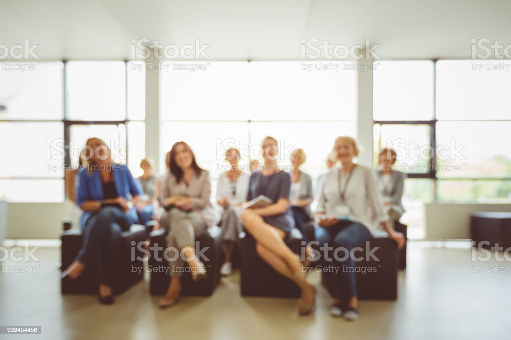 Group of women on seminar, blured image Defocused picture of group of women on conference. Achievement Stock Photo