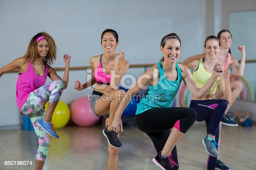 Group of women performing aerobics in fitness studio