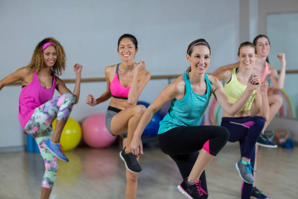 group of women performing aerobics - aerobics stock photos and pictures