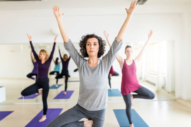 Group of women practicing advanced yoga at gym Mature woman doing yoga, stretching her arms. Group of women practicing advanced yoga at health club. yoga instructor stock pictures, royalty-free photos & images
