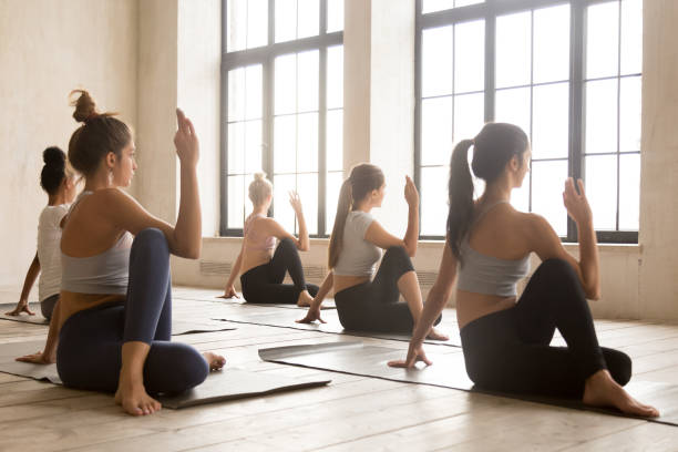 group of women practicing yoga, ardha matsyendrasana pose - twisted stock pictures, royalty-free photos & images