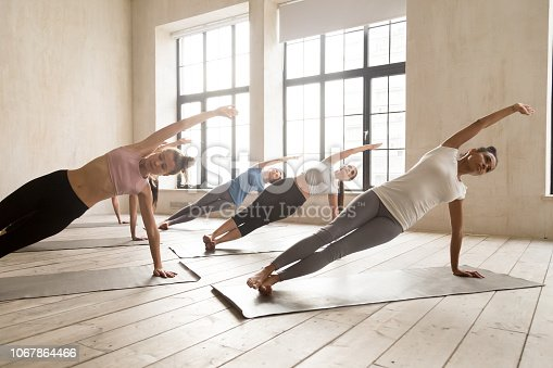 914755448istockphoto Group of women practicing yoga lesson doing Side Plank pose 1067864466
