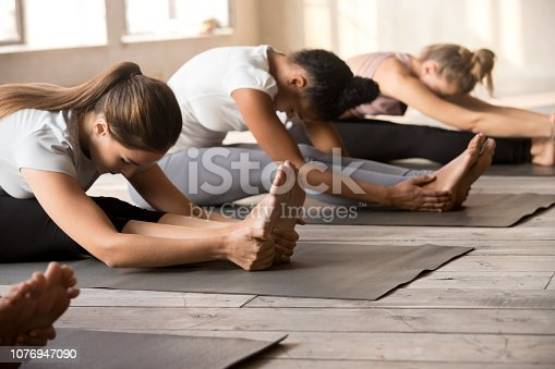 Group of diverse young people practicing yoga lesson, doing Seated forward bend exercise, paschimottanasana pose, mixed race female students training at sport club. Well being, wellness concept
