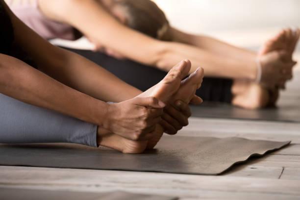 gruppe von frauen, die yoga zu praktizieren, paschimottanasana pose hautnah - yin yoga stock-fotos und bilder