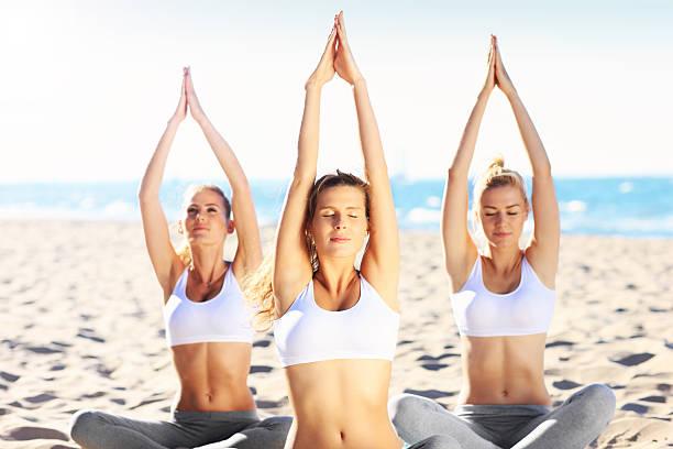 eine gruppe von frauen, die yoga-übungen am strand - wellness ostsee stock-fotos und bilder
