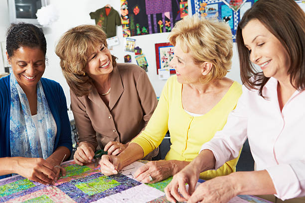 group of women quilting and smiling together - quilt stock photos and pictures