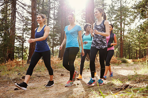 Group of women runners walking in a forest, close up stock photo