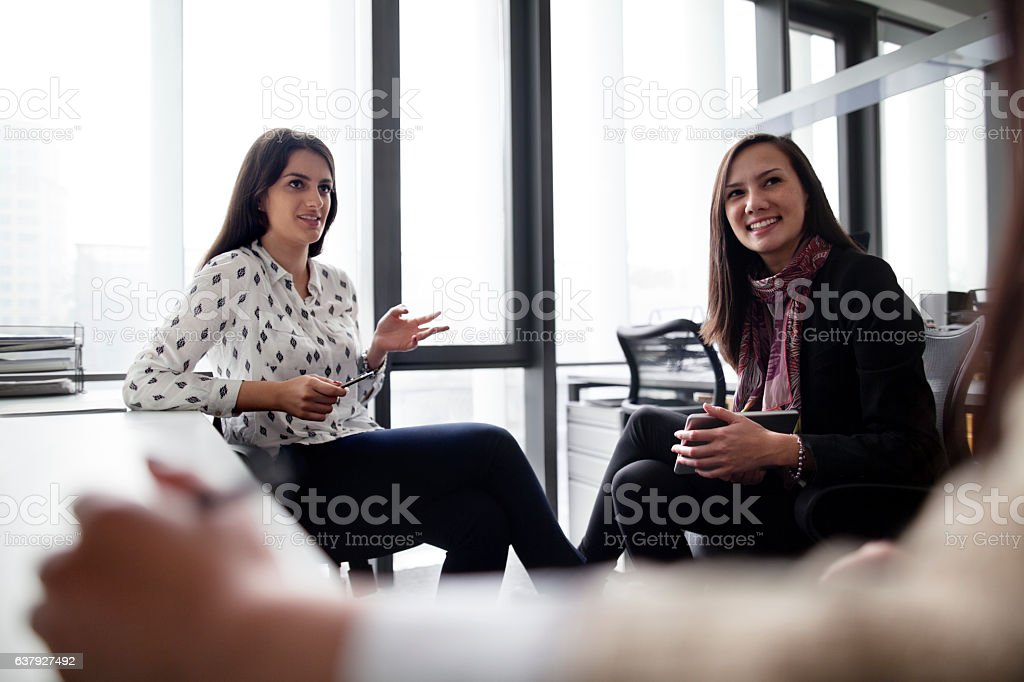 Group of women sitting and talking together in office meeting stock photo