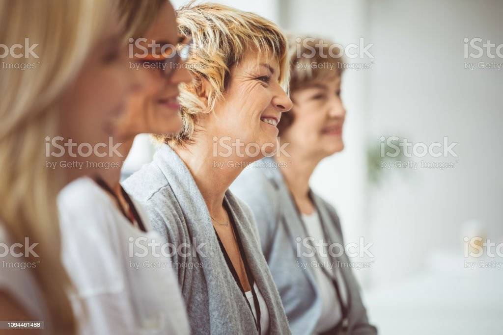Group of women sitting at a seminar Group of women sitting at a seminar and listening to the speaker. Focus on mature woman smiling amongst the group. Achievement Stock Photo