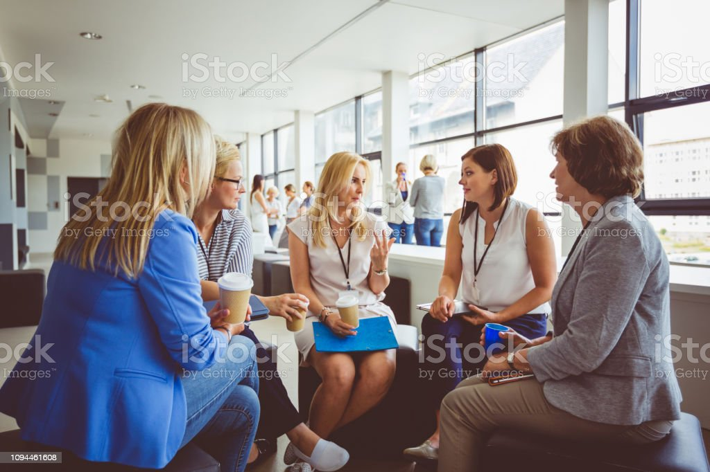 Group of women talking during training session Group of women talking during a training session in modern office. Adult Stock Photo