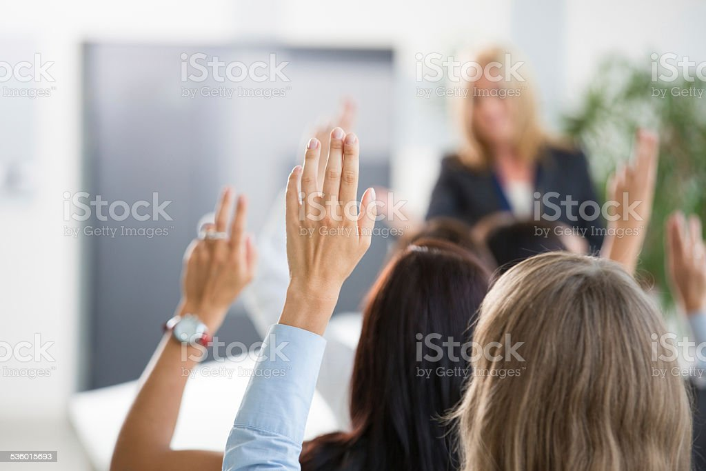 Group of women voting during seminar Group of businesswomen attending a seminar, raising their hands. Focus on hands. Unrecognizable people. 2015 Stock Photo