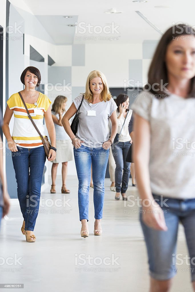 Group of women walking Group of women walking down the hall in modern interior. 30-39 Years Stock Photo