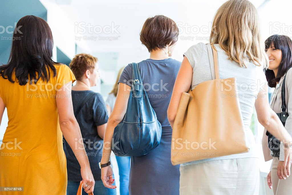 Group of women walking the hall, back view Back view of group of women walking down the hall and discussing. 30-39 Years Stock Photo