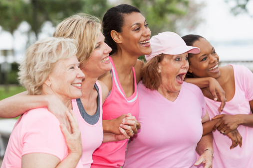 Multi-ethnic group of women (30s, 40s, 60s) wearing pink, participating in breast cancer rally.  Main focus on woman in middle.