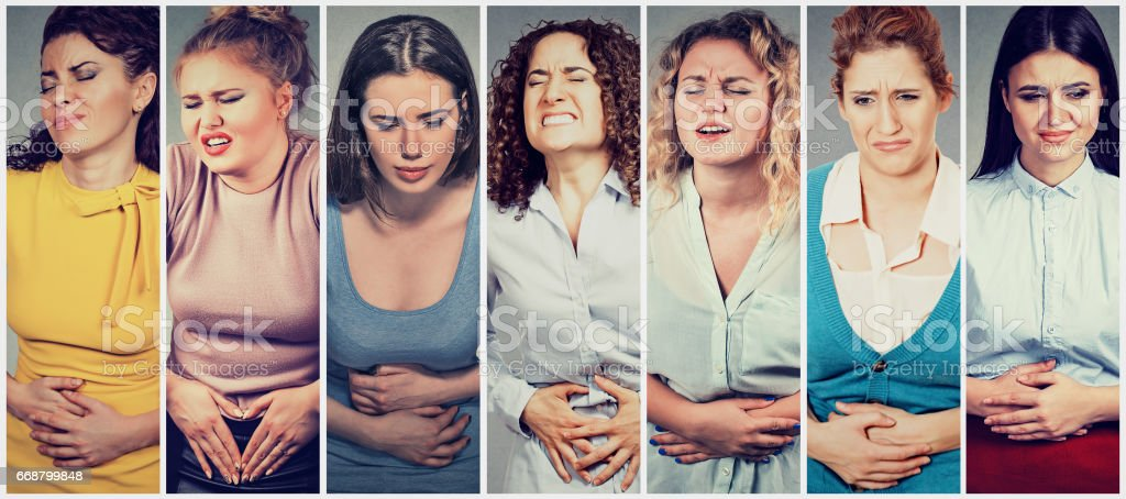 Group of women with hands on stomach having pain stock photo