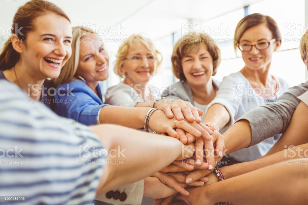 Group of women with their hands stacked Business women with hands stacked during training in the office. Group of women standing in a circle with their hands stacked. A Helping Hand Stock Photo