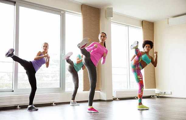 group of women working out and fighting in gym stock photo