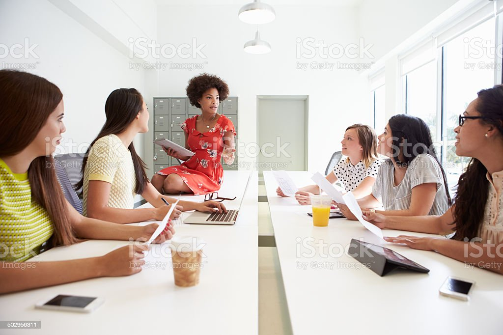 Group Of Women Working Together In Design Studio Group Of Women Working Together In Design Studio Discussing Ideas 20-29 Years Stock Photo