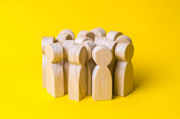group of wooden people figurines on a yellow background. crowd, meeting, social activity. society, social group. herd instinct, management of people. human resources, workers stand together. - icon set healthy foto e immagini stock