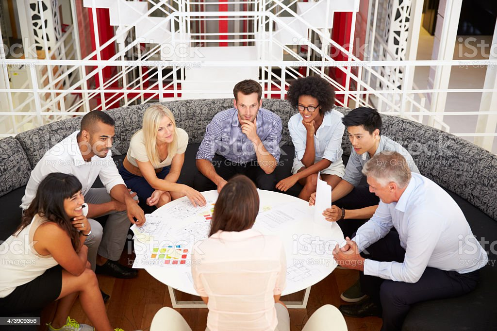 Group of work colleagues having meeting in an office lobby stock photo