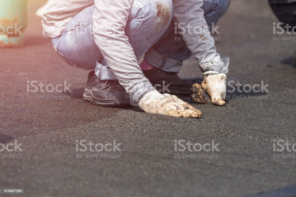 Group of worker installing tar foil on the rooftop of building. Waterproof system by gas and fire torching stock photo