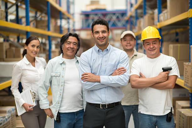group of workers at a warehouse - einzelhandelsarbeiter stock-fotos und bilder