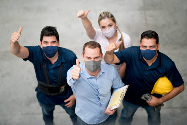 Group of workers at a warehouse wearing facemasks and showing their with thumbs up stock photo