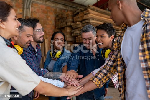 Group of Latin American workers at a wood factory putting their hands together while smiling - labor union concepts