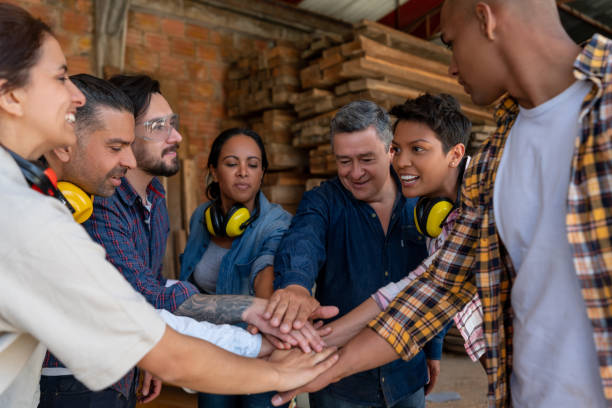 Group of workers at a wood factory putting their hands together Group of Latin American workers at a wood factory putting their hands together while smiling - labor union concepts labor union stock pictures, royalty-free photos & images