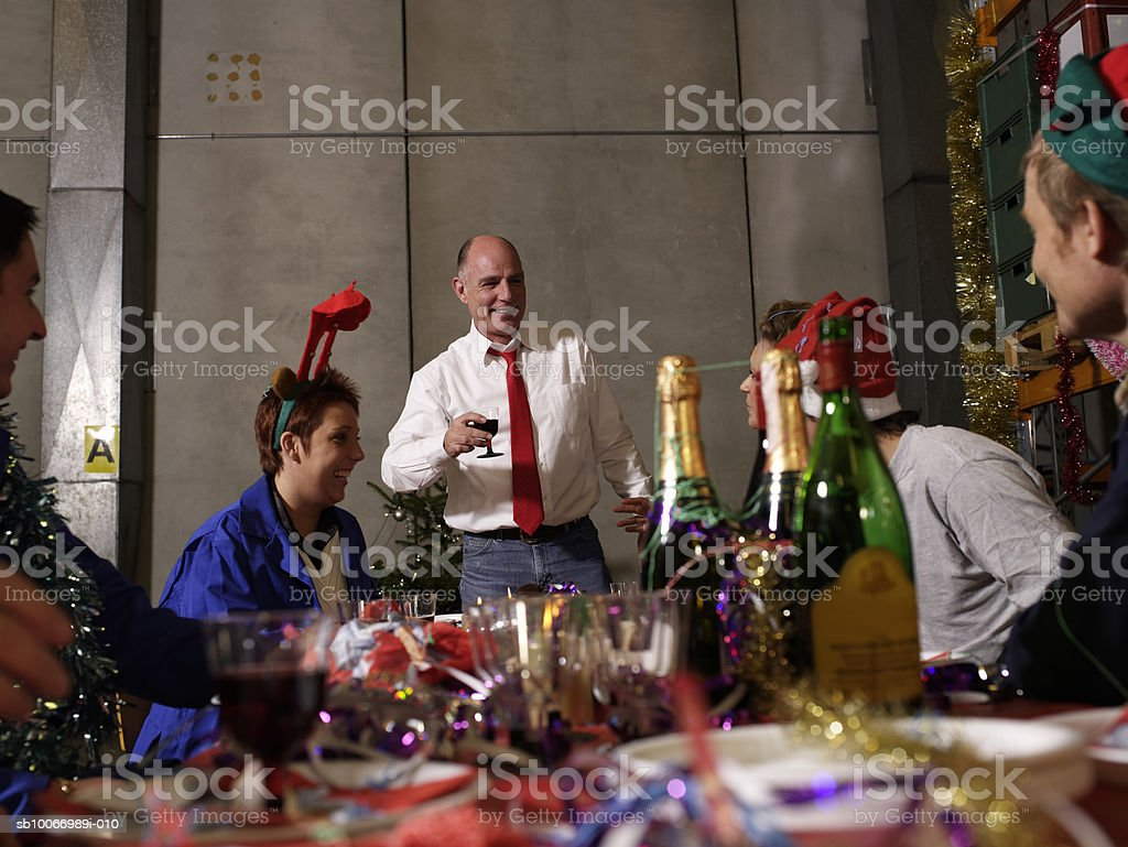 Group of workers celebrating at charismas table in warehouse royalty-free stock photo