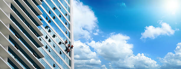 Group of workers cleaning windows on high rise building stock photo
