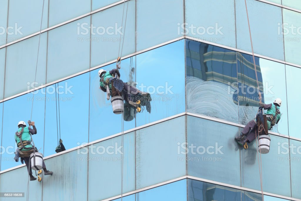 group of workers cleaning windows service on high rise building royalty-free stock photo