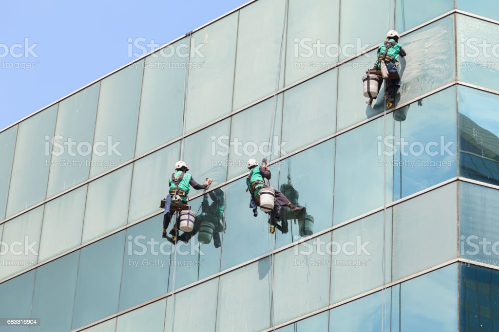 group of workers cleaning windows service on high rise building zbiór zdjęć royalty-free